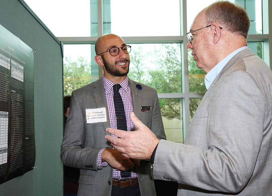 Ali Mahmoud, a Eugene McDermott Scholar and sociology senior, researched the effect of membership in a Muslim fraternity on one's self-confidence and social confidence. He talked with contest judge Dr. Tom Hill PhD'14.