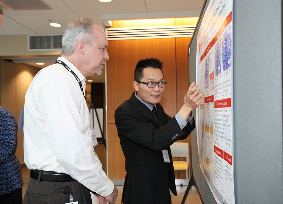 Thong Nguyen, a senior in physics, described his research related to high-energy physics to contest judge Dr. David Thomas.