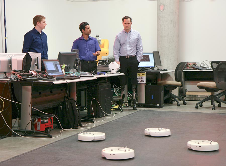 Hugh Herr (right), who heads the biomechatronics research group at the MIT Media Lab, checks out some of the robotics work done by Eckert (left) and research associate Hasan Poonawala.
